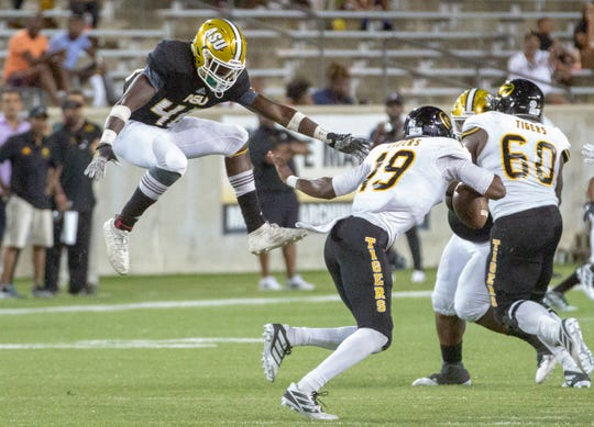 Grambling's Geremy Hickbottom puts his arm out to avoid being jumped on by ASU linebacker Trevor Goodrum (48).