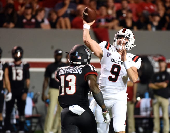 Sep 21, 2019; Raleigh, NC, USA; Ball State Cardinals quarterback Drew Plitt (9) throws a pass as North Carolina State Wolfpack defensive back Tyler Baker-Williams (13) pressures during the first half at Carter-Finley Stadium. Mandatory Credit: Rob Kinnan-USA TODAY Sports
