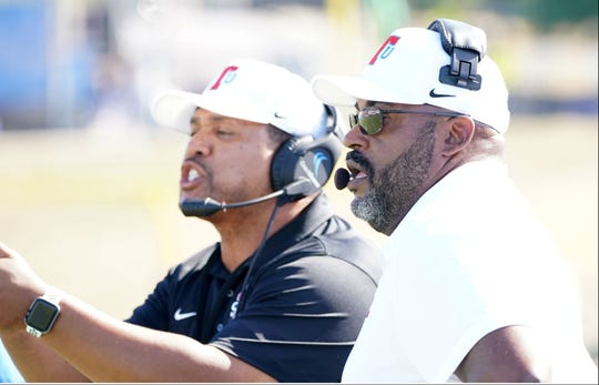 Tennessee State defensive coordinator Garry Fisher, left, gives instruction to the Tigers' defense while coach Rod Reed looks on.