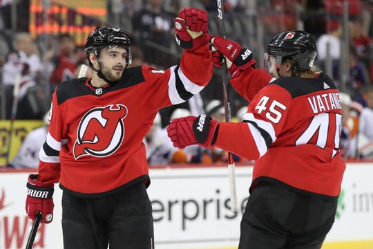 New Jersey Devils defenseman Will Butcher celebrates after scoring a goal with defenseman Sami Vatanen (45) during the second period of a preseason NHL hockey game against the New York Islanders, Saturday, Sept. 21, 2019, in Newark, N.J.