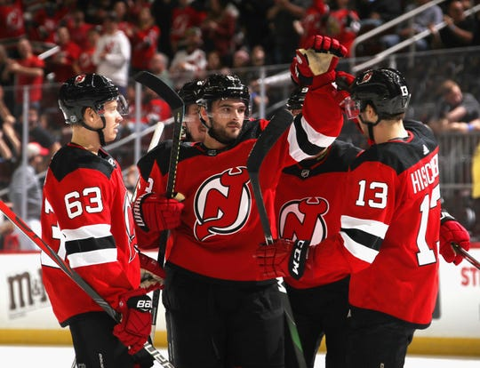 Will Butcher #8 of the New Jersey Devils (C) celebrates his goal at 16:50 of the second period against the New York Islanders and is joined by Jesper Bratt #63 (L) and Nico Hischier #13 (R) at the Prudential Center on September 21, 2019 in Newark, New Jersey.