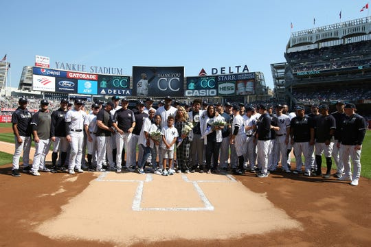 New York Yankees' CC Sabathia, center, surrounded by family and teammates, is honored before a baseball game against the Toronto Blue Jays, Sunday, Sept. 22, 2019, in New York. (AP Photo/Michael Owens)