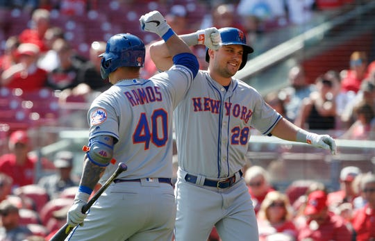 New York Mets' J.D. Davis, right, bumps elbows with Wilson Ramos (40) following a solo home run off Cincinnati Reds starting pitcher Trevor Bauer during the sixth inning of a baseball game, Sunday, Sept. 22, 2019, in Cincinnati. (AP Photo/Gary Landers)