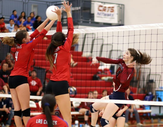Junior Sierra Manos (right) swings away against the Las Cruces double block on Saturday.
