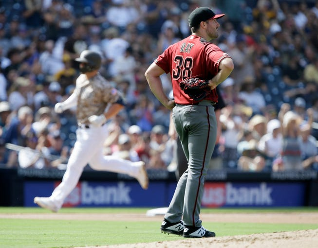 Arizona Diamondbacks starting pitcher Robbie Ray, right, looks away as San Diego Padres' Ty France rounds the bases after hitting a two-run home run during the fourth inning of a baseball game in San Diego, Sunday, Sept. 22, 2019.