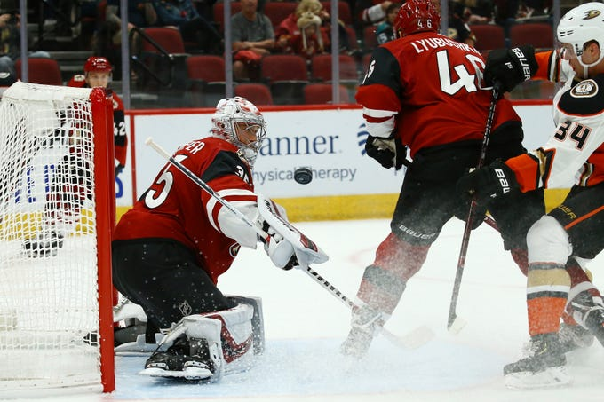 Arizona Coyotes goaltender Darcy Kuemper, left, makes a save on a shot by Anaheim Ducks center Sam Steel (34) as Coyotes defenseman Ilya Lyubushkin, middle, helps out during the first period of a preseason NHL hockey game Saturday, Sept. 21, 2019, in Glendale, Ariz. (AP Photo/Ross D. Franklin)