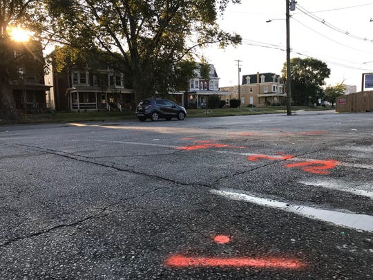 York shooting: Spray-paint from detectives marks the scene where York City Police say they found one man dead and another severely injured early this morning in a parking lot in the 500 block of North George Street.