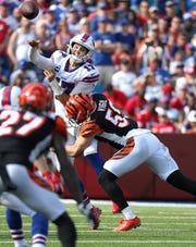 Bills quarterback Josh Allen is hit by Bengals Nick Vigil as he releases the ball.