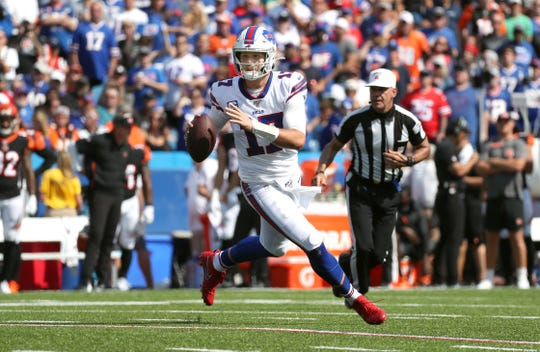 Buffalo Bills quarterback Josh Allen rolls to his left and looks to pass against the Bengals.