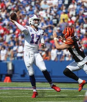 Bills quarterback Josh Allen makes an off balance pass while under pressure by Bengals Nick Vigil.