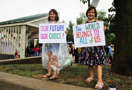 Sisters Delilah and Nora Phipps hold signs during a climate strike at Park Central Square in Springfield Sunday, Sept. 22, 2019.