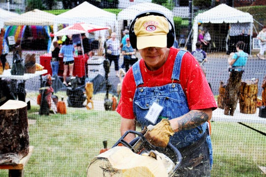 Jenny Tanner, of Mosshill Creek Carver, uses a chain saw to create art from a tree trunk during the 22nd annual Cider Days Sunday, Sept. 22, 2019, in Springfield, Mo.