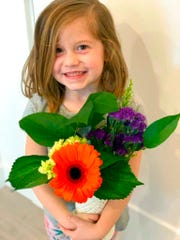 This Feb. 14, 2019 photo provided by her uncle, David Smith, shows Aria Hill posing with flowers near Eagle Mountain in northern Utah during a family trip. Kellen Hill, whose errant golf shot killed his 6-year-old daughter, says his drive went nearly straight left and through the back of a golf cart where she was sitting. Kellen and his wife have returned to the golf course in an attempt to make it a place where they can fondly remember their daughter, the Deseret News reports. (David Smith via AP, File)