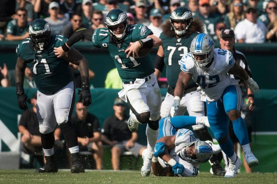 Eagles' Carson Wentz (11) scrambles for yards under pressure from the Detroit defense Sunday at Lincoln Financial Field. The Lions defeated the Eagles 27-24.
