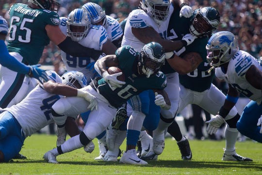 Eagles' Miles Sanders (26) is brought down by the Lions defense Sunday at Lincoln Financial Field. The Lions defeated the Eagles 27-24.