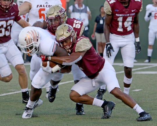 Midwestern State's Melik Owens (55) and Marcus Wilkerson (11) tackle UTPB's Davion Sutton Saturday, Sept. 21, 2019, at Memorial Stadium.