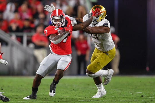 Georgia running back D'Andre Swift fights off the tackle of Notre Dame defensive lineman Khalid Kareem  during the first half at Sanford Stadium.