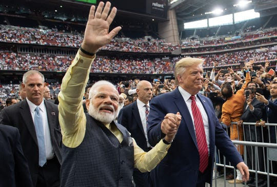 """President Donald Trump and Indian Prime Minister Narendra Modi attend """"Howdy, Modi!"""" at NRG Stadium in Houston, Texas, September 22, 2019. Tens of thousands of Indian-Americans converged on Houston on Sunday for an unusual joint rally by Donald Trump and Narendra Modi, a visible symbol of the bond between the nationalist-minded leaders. With many in the crowd decked out in formal Indian attire or the signature saffron of Modi's Bharatiya Janata Party, the event kicked off in a football stadium with a Sikh blessing, boisterous bhangra dancing and, in a nod to local customs, cheerleaders in cowboy hats."""