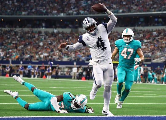 Dallas Cowboys quarterback Dak Prescott (4) scores a third quarter touchdown against Miami Dolphins safety Walt Aikens (35) at AT&T Stadium.