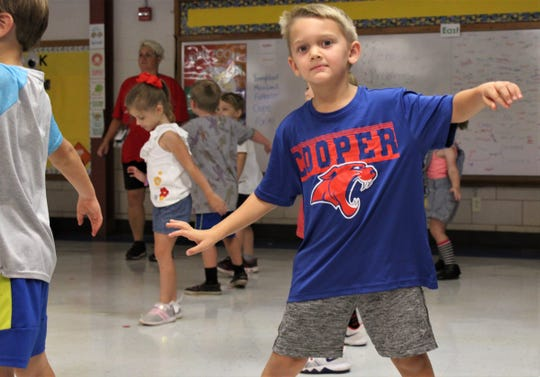 Colt Haddock freezes in place near his dot during a morning workout conducted by Marsha Hamilton at Austin Elementary School. PE classes are in classrooms because the school does not have a gym this fall. Sept. 2019