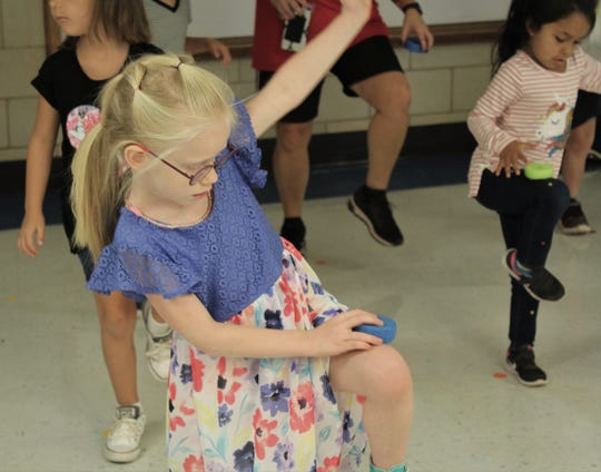 """Kadence Kitchens tries to stay upright while placing a """"donut"""" on her left knee during an exercise period at Austin Elementary School. September 2019"""