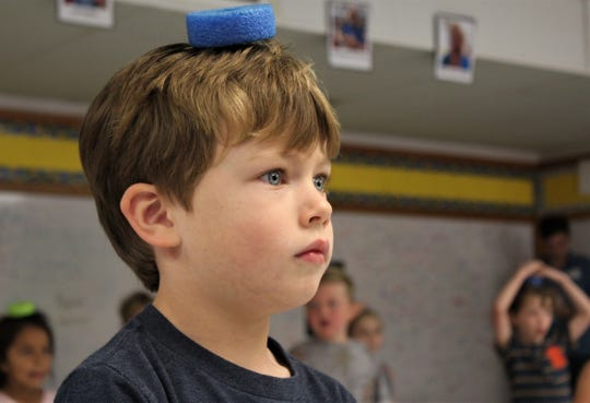 Blaine Lawrence balances a foam oval, or donut, on his head, looking attentively at teacher Marsha Hamilton during a recent physical education period in a classroom at Austin Elementary School, which this school year is without a gymnasium. Sept 2019