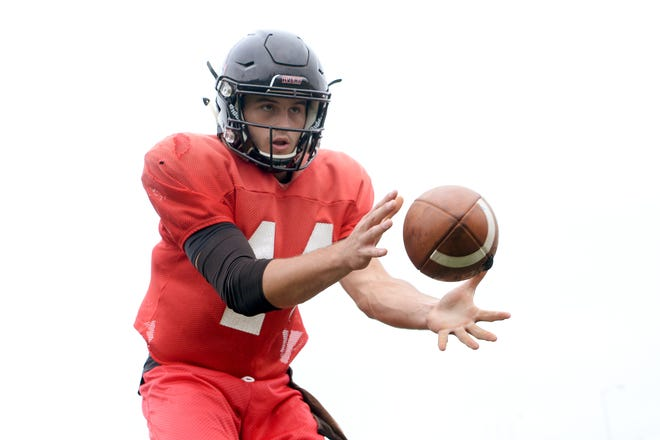 Avery County junior quarterback Troy Hoilman prepares to throws a pass during practice at Avery County High School in Newland on Sept. 18, 2019.