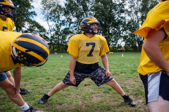 Climax-Scotts senior Blake Borden stretches before football practice on Monday, Sept. 23, 2019 in Climax, Mich. Borden was born with severe clubfoot, a condition in which his feet were twisted down and inward.