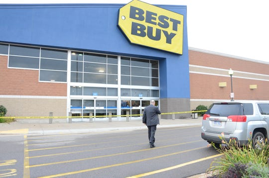 A detective enters Best Buy Monday after a robbery.