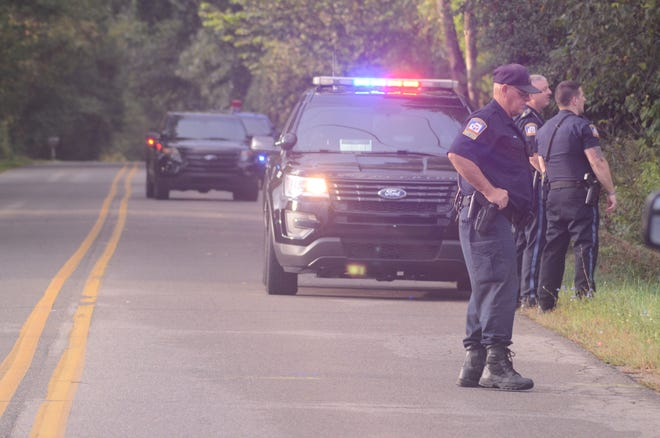 Police wait along Six-Mile Road while other officers search in woods for suspects after a robbery Monday.