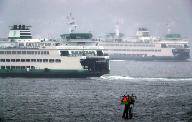 The Washington State Ferries Wenatchee and Tacoma pass in the fog and rain as they work the Bainbridge Island to Seattle route on Sunday, September 22, 2019
