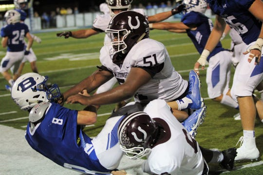 Owen senior defensive end Jaylin Davidson (51) tackles Brevard senior quarterback Baxter Swicegood on Sept. 20.