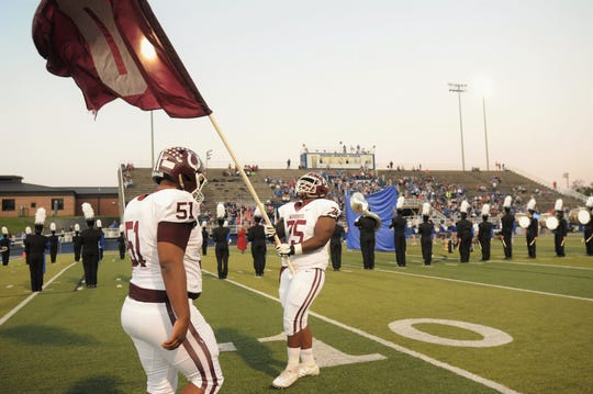 Owen senior offensive and defensive lineman Saevion Gibbs carries his team's flag onto the field at Brevard Memorial Stadium on Sept. 20.