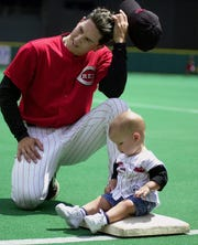 Cincinnati Reds pitcher Danny Graves scratches his head while sitting with his 10-month-old son Trey on first base during the players-family game before the Reds game against Arizona July 23, 2000 at Cinergy Field.