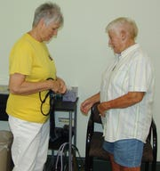 Ruby Lyons and Pat Miller demonstrate a blood pressure monitor during the open house that was held to honor the 10th anniversary of the Hope Clinic.