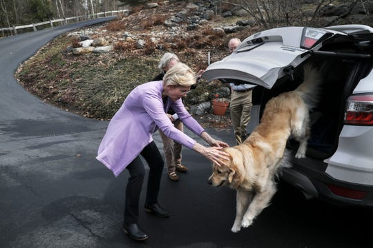 Sen. Elizabeth Warren D-Mass., lets her dog Bailey out of the car as she arrives at the home of Ann Garland in Lebanon, N.H. Saturday, April 13, 2019.