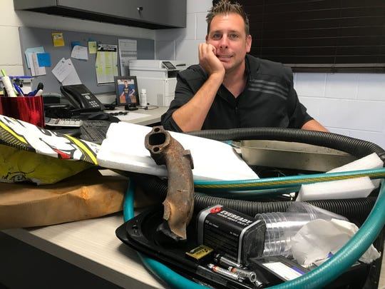 Lucas Dean, supervisor of the big SOCRRA recycling center in Troy, sits with his desk full of trash --  all items that shouldn't go into recycling carts or bins