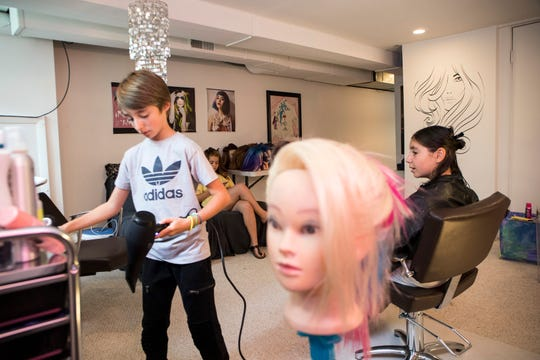 From left, Vince Weishaus, 11 serves clients Jamie Bloom, 11 of Franklin and Hannah Byer, 11 of Birmingham in his basement hair salon in Bloomfield Hills, Mich., Sunday, Sept. 22, 2019.