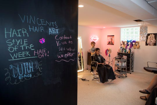 Vince Weishaus, 11 dishes news with Hannah Byer, 11 of Birmingham as he dries her hair in his basement salon in Bloomfield Hills, Mich., Sunday, Sept. 22, 2019.