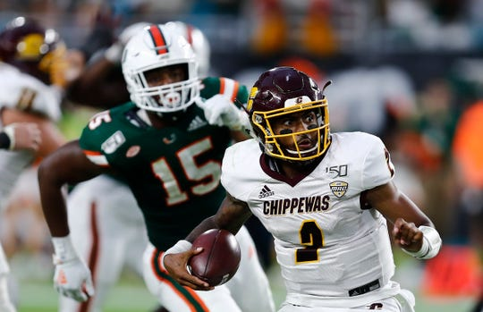 Central Michigan quarterback David Moore runs with the ball against Miami defensive lineman Gregory Rousseau during the second half.