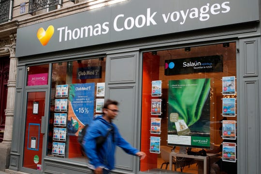 People walk past a Thomas Cook travel shop in Paris.