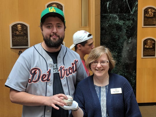 Ely Hydes hands the Albert Pujols baseball to Susan MacKay, director of collections for the Baseball Hall of Fame.