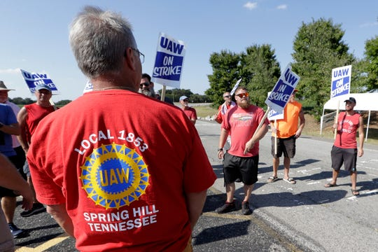 Tim Stannard, front left, president of United Auto Workers Local 1853, talks with striking workers at the General Motors plant in Spring Hill, Tennessee. A judge on Monday issued a temporary restraining order to prevent striking workers from blocking access to the facility. GM had submitted a complaint stating picketers had prevented access to the plant, placed screws and nails on the roadway, threatened motorists and damaged vehicles.