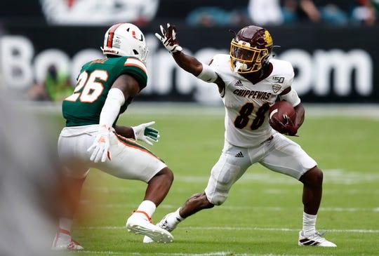 Central Michigan wide receiver Kalil Pimpleton prepares to stiff-arm Miami defensive back Gurvan Hall Jr.