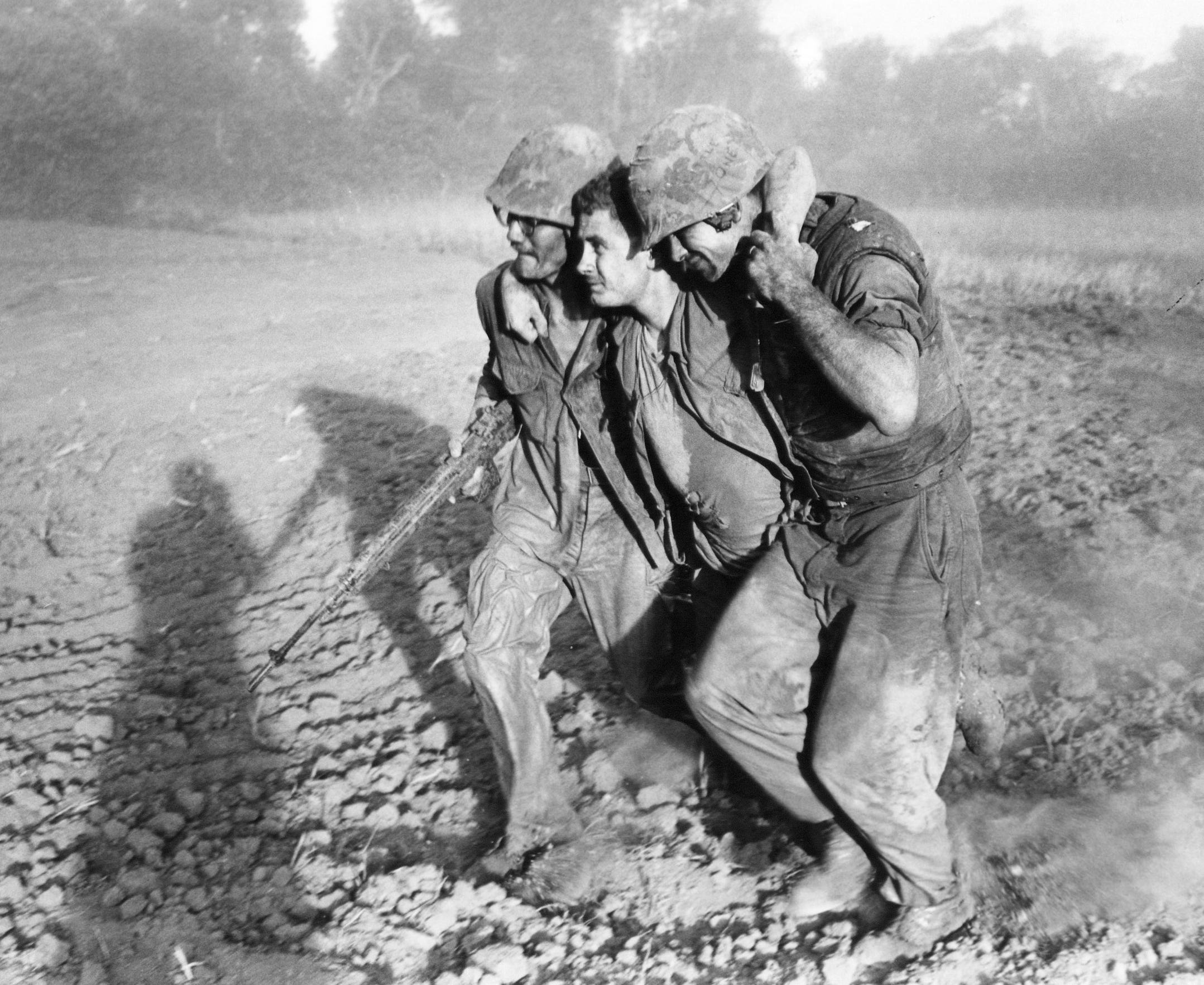 In this Aug. 19, 1965 photo, a wounded U.S. Marine is helped by two other Marines to an evacuation helicopter near Van Tuong, Vietnam.  Hattie and Jim Ford speculate that the reason Army Lt. Deane Taylor Jr. didn't run when his helicopter crashed in Vietnam was that one of the three crash survivors had a broken leg.