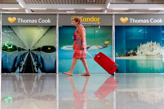 A passenger walks past a closed Thomas Cook office at Palma de Mallorca airport on Monday, Sept. 23, 2019.