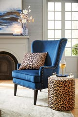 Leopard print acts as a neutral when it joins other colors like the blue chair shown here that's embellished with a patterned pillow and an ottoman turned side table.