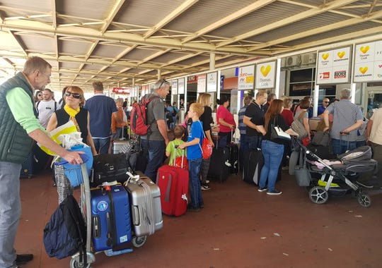 British passengers with Thomas Cook wait in queue at Antalya airport in Antalya, Turkey, Monday Sept. 23, 2019.