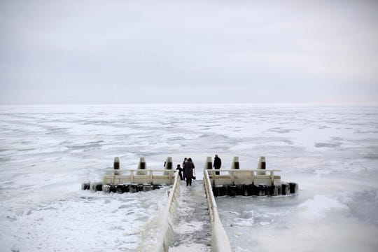 In this image taken Thursday Feb. 9, 2012, Tourists admire the frozen IJsselmeer inland sea on Afsluitdijk, a dike closing off the Wadden sea and North Sea from IJsselmeer inland sea, northern Netherlands.