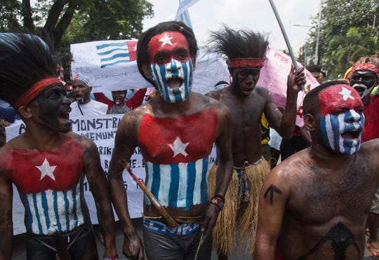 Papuan students, with their body and face painted with the colors of the banned separatist 'Morning Star' flag, shout slogans during a rally in Medan, North Sumatra, Indonesia, Saturday, Aug. 31, 2019.